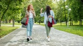 stile etnico : Excited friends girls doing high-five during walk in park with colorful shopping bags chatting laughing. Modern lifestyle, shopaholism and friendship concept.