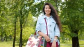 adolescencia : Portrait of pretty Asian girl standing in park with shopping bags smiling looking at camera wearing trendy clothing. Fashion, people and lifestyle concept.