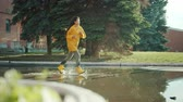 à prova d'água : Beautiful Asian woman student is running in puddles wearing wet clothing raincoat and gumboots enjoying joyful activity. Youth, weather and people concept. Stock Footage