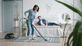 halı : Slow motion of happy girl vacuuming floor in bedroom while guy husband lying in bed having fun on clean-up day. People, housework and relationship concept.