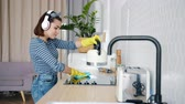 опрятный : Slow motion of young lady cleaning kitchen and listening to music in headphones enjoying song and housework in apartment. Youth and fun concept. Стоковые видеозаписи