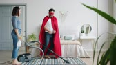 ヒーロー : superhero is dancing with vacuum cleaner then running away when woman is coming home with bottle sprayer. Lifestyle, housework and fun concept.