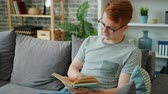 čtenář : Smiling young man in glasses is reading book sitting on couch in apartment enjoying leisure time at home. Adolescence, hobby and smart youth concept. Dostupné videozáznamy