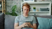 Teenager in wireless headphones is using smartphone touching screen enjoying music relaxing on couch at home. Modern technology and youth concept.