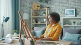 Young African American woman is painting at home at table then looking at picture smiling enjoying artwork. Lifestyle, hobby and creative people concept.