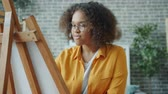 Slow motion of cheerful African American girl painting picture at home working with wooden easel creating image. Fine arts, youth and creativity concept.