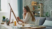 adolescencia : Young woman designer is drawing picture at home sitting at easel in apartment using colored pencils. Creative people, occupation and students concept. Archivo de Video