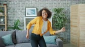 Carefree young lady African American student is having fun at home dancing listening to music looking at camera. Modern lifestyle, happiness and dance concept.