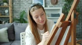 Slow motion of happy teenage girl painting at home alone using easel, paper and pencils enjoying creative hobby. Modern people, adolescence and house concept. Vídeos