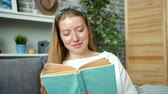 sardas : Portrait of attractive teenage girl reading interesting book at home smiling turning pages sitting on couch in apartment. Students, hobby and literature concept.