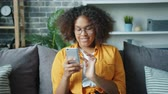 Beautiful African American girl student is using smartphone and laughing relaxing on comfortable sofa at home. Modern technology and youth lifestyle concept.