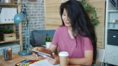 Pretty Asian girl in casual clothing is using tablet working at desk in modern office alone. Modern technology, workplace and contemporary devices concept. Dostupné videozáznamy