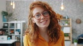 Portrait of beautiful young lady in trendy glasses looking at camera in office smiling wearing casual clothing. Modern youth, workplace and emotions concept. Vídeos