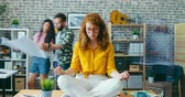 Zoom-out time-lapse portrait of attractive young lady sitting on office desk in lotus pose relaxing on workday. Stress management and modern youth concept. Dostupné videozáznamy