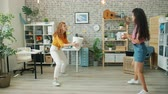 Young ladies throwing paper balls in basket in office enjoying funny game in workplace having fun. Joyful people, entertainment and business concept.