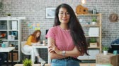 Portrait of attractive Asian lady standing indoors in office with arms crossed smiling looking at camera while multi-ethnic group of people working in background.