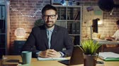 osobnost : Joyful businessman in glasses is smiling in office in the evening sitting at desk and looking at camera. Modern business, happy people and emotions concept. Dostupné videozáznamy