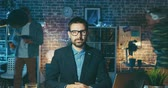 ctižádost : Zoom-in time lapse portrait of good-looking guy in glasses sitting at desk in office at night looking at camera with serious face. People and profession concept. Dostupné videozáznamy