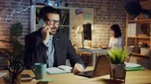 overwerk : Joyful entrepreneur speaking on mobile phone in workplace at night smiling discussing business sitting at desk while coworker is working in background. People and job concept.