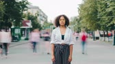aussenseiter : Time lapse of attractive African American girl standing alone in city street while people male and female are moving around. Youth and casual life concept.