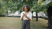 prohlížení : Portrait of cheerful African American girl using smartphone outdoors smiling having fun standing alone in city park. People, devices and internet concept.