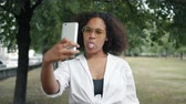 Portrait of happy African American student taking selfie outdoors with smartphone camera posing standing outside in urban park. People and photo concept.