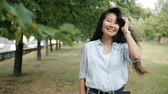 Portrait of attractive Asian lady smiling touching hair looking at camera outdoors in city park on summer day. Modern lifestyle, people and nature concept.