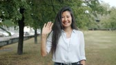 Slow motion portrait of young Asian girl waving hand smiling looking at camera outdoors in urban park. Millennials, positive emotions and happy youth concept.