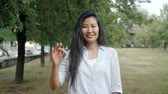 Beautiful Asian woman showing OK hand gesture outside in city park smiling looking at camera alone. Cheerful people, emotions and lifestyle concept.