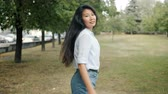 Slow motion of slender Asian lady walking outdoors in green park then turning and looking at camera with happy face. Modern lifestyle and people concept.