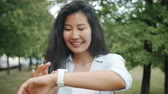 Happy Asian girl is using smartwatch touching screen in city park in summer enjoying cool gadget. Modern technology and cheerful youth concept.