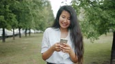 mensageiro : Asian young woman using smartphone in park laughing touching screen enjoying modern device and nature on summer day. People and modern lifestyle concept.