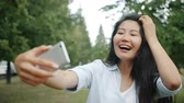 Slow motion of beautiful Asian girl taking selfie outdoors with smartphone camera standing outside in city park. People, lifestyle and photo concept.