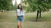 Slow motion of happy Asian girl in trendy clothing dancing in city park smiling enjoying leisure time and nature. People, lifestyle and happiness concept. Dostupné videozáznamy