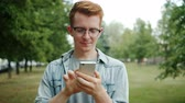 Young handsome man using smartphone in park touching screen enjoying modern device and remote communication. People, devices and modern lifestyle concept. Stockvideo