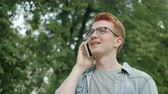 Attractive young businessman in glasses is talking on mobile phone outdoors in city park smiling discussing business. People, communication and youth concept.