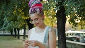Stylish young lady with colorful hair and piercing is using smart phone outside in park smiling enjoying social media. Technology and modern lifestyle concept.
