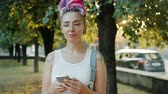 Cute girl with colorful hair and piercing is using smartphone smiling standing outdoors in city park enjoying modern technology, Youth and technology concept.