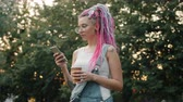 Pretty student with colored hair and tattoo is using smartphone holding coffee standing outdoors in park on summer day. Youth and urban lifestyle concept.