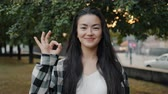 Pretty Asian student showing OK hand gesture outdoors in urban park smiling looking at camera. Cheerful people, positive emotions and lifestyle concept. Stockvideo