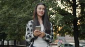 Cute Asian girl is touching smartphone screen in urban park standing alone smiling holding electronic device. Lifestyle, technology and communication concept.