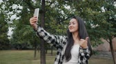 Portrait of attractive Asian girl taking selfie in green city park with smartphone camera standing outside alone. People, lifestyle and photo concept. Dostupné videozáznamy