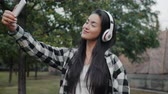 Cute Asian girl wearing headphones is taking selfie with smartphone camera outdoors posing smiling enjoying music and having fun alone in city street.