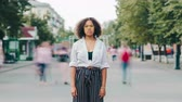 Time lapse of pretty Afro-American student serious girl standing in urban street outdoors looking at camera. Individuality, character and casual life concept.