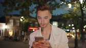 Slow motion of attractive student using smartphone touching screen outdoors standing in city street at night . Devices, people and modern youth concept. Vídeos