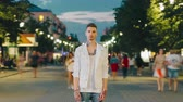 Time lapse portrait of tattoed student standing in urban pedestrian street at night looking at camera with serious expression. People and lifestyle concept.