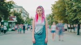 Time lapse portrait of beautiful hipster girl with bright hair and tattoo outside in pedestrian street looking at camera. Youth culture, stylish people and city concept.