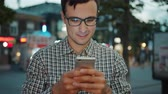 Portrait of attractive young man in glasses using smartphone touching screen outdoors standing in city street alone. Devices, people and modern youth concept.