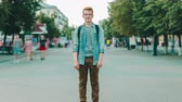 Zoom in time lapse portrait of attractive guy student outdoors in busy urban street looking at camera. Modern people, casual life and summer in city concept. Dostupné videozáznamy