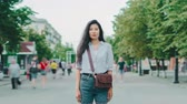 Portrait of beautiful Asian girl student stanidng in busy city street with serious face looking at camere while people men and women are walking around. Dostupné videozáznamy